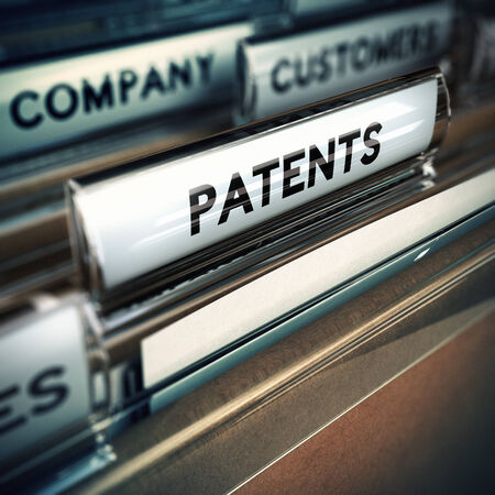company innovation: Folder and focus on a tab with the word patents, blur effect  Concept of company innovation    Stock Photo