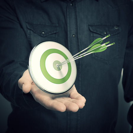 targets: one hand with a green target and three arrows, Symbol of marketing solutions or successful company advertising, blur effect  Stock Photo