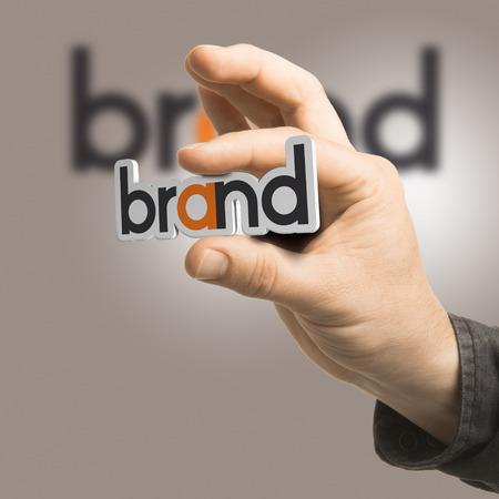 한 손으로는 베이지 색 배경 브랜딩 개념 이미지를 통해 단어의 브랜드를 들고 2D 그림, 3D 렌더링 및 사진 사이의 구성입니다