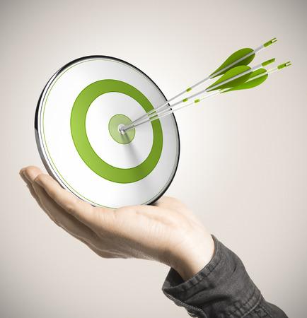 ベージュ色の背景のビジネス パフォーマンスの概念上のセンターを打つ 3 つの矢印の付いた緑のターゲットを持っている手