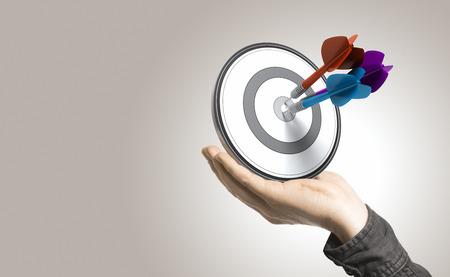 한 손으로 3 개의 다트 중심, 제어 및 효율적인 비즈니스 솔루션의 베이지 색 배경 그림 타격 목표를 잡고 스톡 콘텐츠