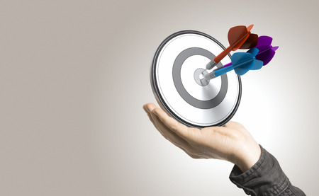 One hand holding a target with three darts hitting the center, beige background Illustration of control and effective business solutions