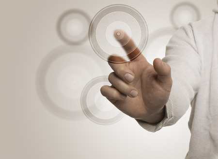 Man hand touching a transparent target with the index, beige background. Image suitable for a Marketing Concept or Business solutions with free space for text on the left  photo