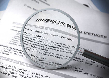 recruit: French resume with magnifier and focus on the word engineer, blur effect