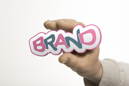 One hand holding the word brand over a white background  Company identity concept  The image is a composition between 3D rendering and photography photo