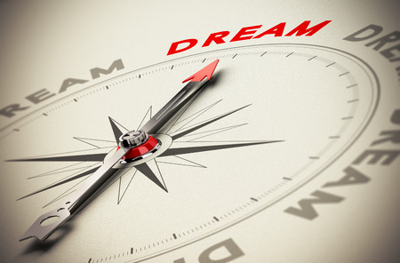 Compass with red needle pointing the word dream, beige paper background, symbol of achieving dreams