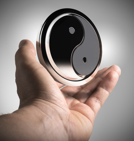 interdependence: Hand holding Yin Yang symbol over grey background. Harmony concept