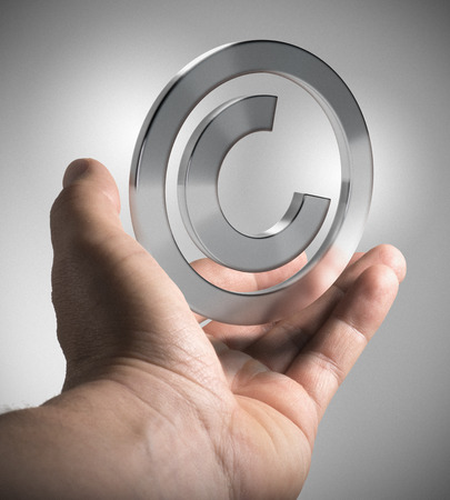 copyright: Man hand holding copyright symbol over grey background, concept image for illustration  of intellectual property. Stock Photo