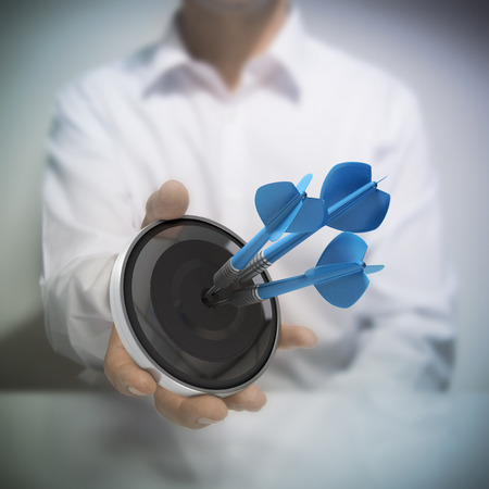 Man holding on black target with three blue darts hitting the center. photo
