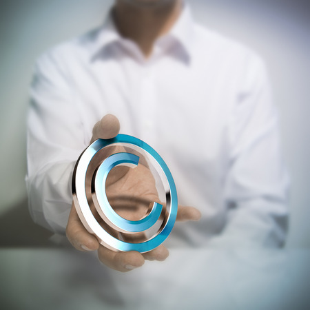 copyright: Man holding metallic copyright symbol. Concept image for illustration of author protection or intellectual property Stock Photo