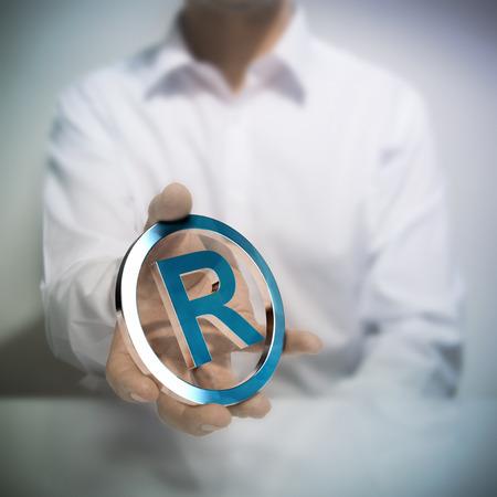 r image: Man holding simbolo di marchio registrato metallico. Concetto di immagine per l'illustrazione della propriet� intellettuale o la tutela dei prodotti o servizi. Archivio Fotografico