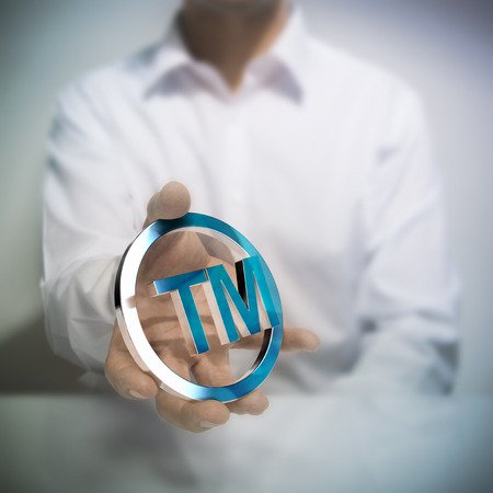 property rights: Man holding metallic trademark symbol. Concept image for illustration of intellectual property or protection of products or services.