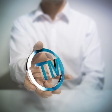 Man holding simbolo di marchio metallico. Concetto di immagine per l'illustrazione della proprietà intellettuale o la tutela dei prodotti o servizi. Archivio Fotografico - 32841490