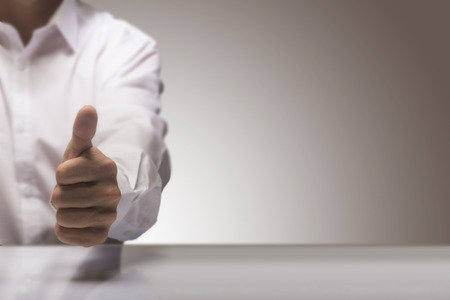 ottimo: L'uomo con un pollice in alto sullo sfondo di un tavolo lucido e copia spazio a destra, concetto di immagine per l'illustrazione di un servizio di qualità eccellente. Archivio Fotografico