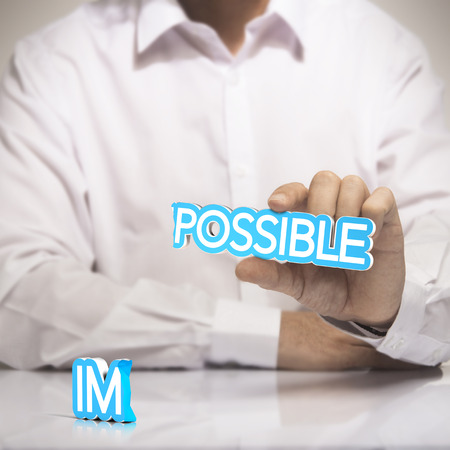 One man holding the word possible in one hand with  the prefix