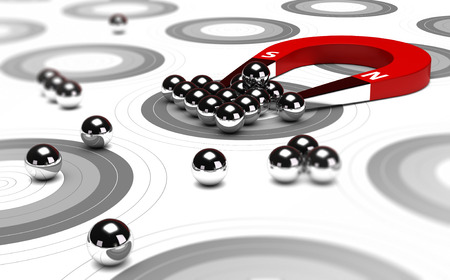 Horseshoe magnet attracting metal balls in the center of a grey target. Image concept of inbound marketing or advertising. Standard-Bild