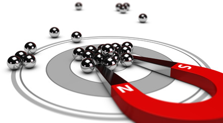 Horseshoe magnet attracting metal balls in the center of a grey target. Image concept of inbound marketing or advertising. Archivio Fotografico