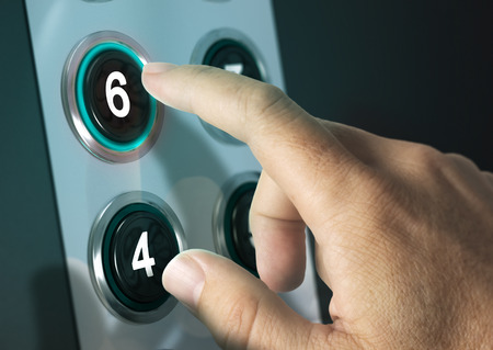 blue button: Elevator buttons with finger pressing the number six, concept of choice Stock Photo