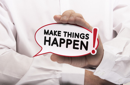 achieve goal: Image of a man hand holding speech balloon with the text make things happen, white shirt. Concept for motivation and goal achievement.