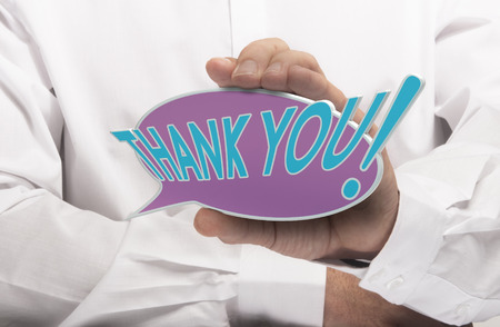 acknowledgment: Image of a man hand holding speech balloon with the text thank you, white shirt. Concept for acknowledgment and thanks.