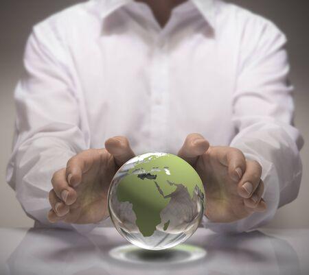 educacion ambiental: Imagen de un hombre de camisa blanca proteger un vidrio tierra con sus manos. Concepto de la tierra para la protección del medio ambiente o de negocios global.