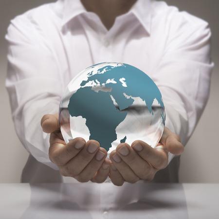educacion ambiental: Imagen de un hombre de camisa blanca que sostiene en sus manos una tierra de cristal. Concepto de la tierra para el cuidado y protección del medio ambiente o de negocios global.