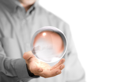 Caucasian man holding a glass or crystal ball, copy space on the left side of the image. Magician or fortuneteller background concept over white.