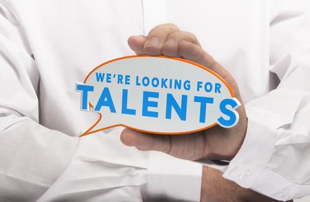 puesto de trabajo: Hombre que sostiene una burbuja de c�mics con el texto que estamos buscando talentos. Imagen del concepto de ilustraci�n de captaci�n de talento o de oportunidades de trabajo. Foto de archivo
