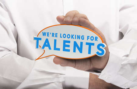 talent management: Man holding a comics bubble with the text we are looking for talents. Concept image for illustration of talent recruitment or job opportunities.