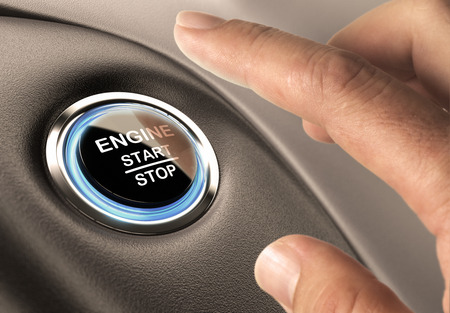 Car engine start and stop button with blue light and black textured background, close up and one finger Фото со стока