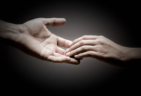 helping up: two hands are touching each other over black background, concept of solidarity or empathy. Stock Photo