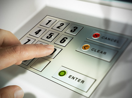cashpoint: Finger about to press a pin code on a pad. Security code on an Automated Teller Machine, ATM