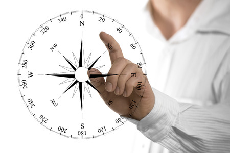 Finger about to touch a compass rose over white background. Concept of orientation.