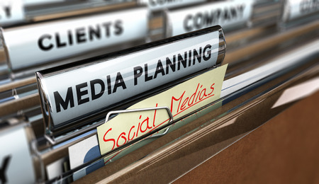 Close up on a file tab with the text media planning plus a note where it is handwritten social medias Blur effect. Concept image for illustration of communication or advertising agency
