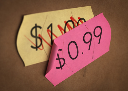 price label: Psychological pricing printed on a pink label over a normal price. Concept image for illustration of prices psychological impact. Stock Photo
