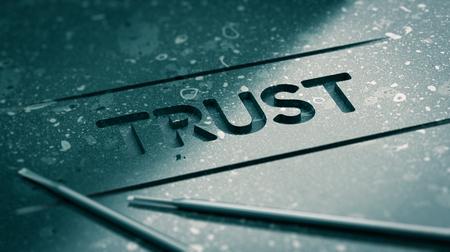 Palavra confiança gravado em pedra preta com ferramentas e efeito de borrão. Imagem do conceito para ilustração de forte relacionamento ou parceria e fé.