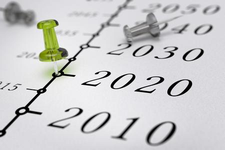 21e siècle calendrier sur fond de papier blanc avec punaise verte pointant vers l'année 2020, l'effet de flou, image conceptuelle. Banque d'images