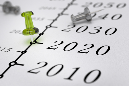 long term: 21st Century timeline over white paper background with green pushpin pointing the year 2020, blur effect, conceptual image. Stock Photo