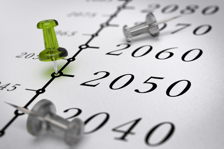 21st Century timeline over paper background with green pushpin pointing the year 2050, blur effect, conceptual image. Stock Photo
