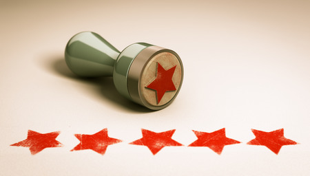 reviewing: Rubber stamp over paper background with five stars printed on it. concept image for illustration of high customer experience and quality level Stock Photo