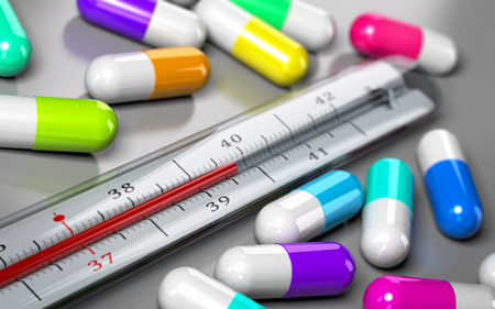 thermometer with many pills around it over grey background. Concept image for illustration of over consumption of drugs and antibiotics.