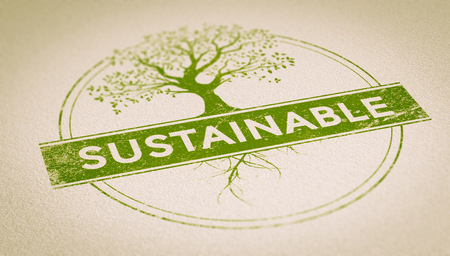 Green rubber stamp imprint on a sheet of paper composed of a tree and the word sustainable inside a circle with depth of field effect. Concept image for illustration of sustainability and environment. Stock Photo