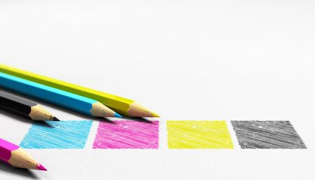 Four colors cian magenta yellow and black handwritten on a paper texture with 4 wooden pencils sourounding it . Concept image for graphic design and prepress.