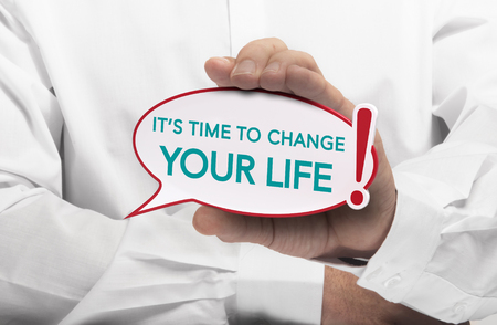 text bubble: Image of a man hand holding speech bubble with the text it is time to change your life, white shirt. Conceptual message for motivation and goal achievement.