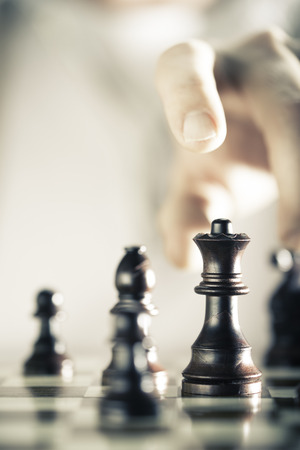 Vertical Image of a chess game with focus on the queen and a blurry hand at the background