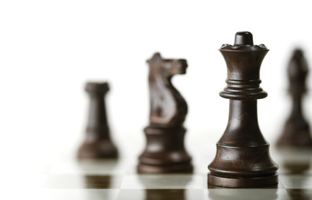 white board: Horizontal image of a chess game with focus on the queen and a blurry pieces over white background