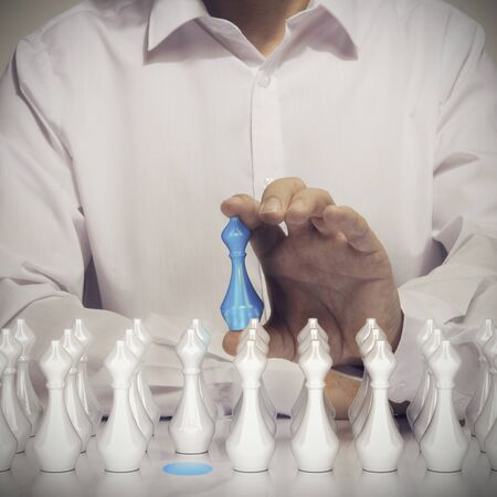 Business talents acquisition concept, Conceptual image of a man hand holding a blue pawn with many other white pawns at the foreground.