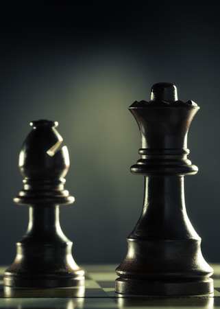 the anticipation: Vertical image of a chess game with focus on the queen over dark background, Concept of management or business anticipation.