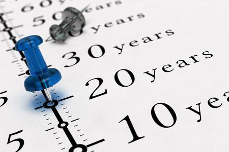 cronologia: 20 años escritas en un papel con una imagen del concepto de chincheta azul, para la visión de negocio o largo plazo prospectivo. El número dos mil veinticinco. Foto de archivo
