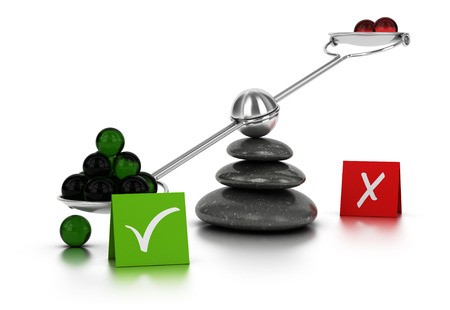 Green and red spheres on a seesaw with three black pebbles over white background. Concept image for illustration of for or against dilemma.